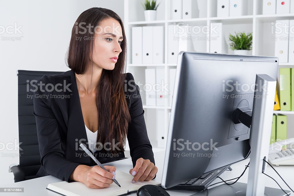 Serious businesswoman with long hair taking notes stock photo