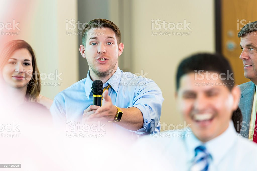 Serious Caucasian man questions a candidate during town hall meeting stock photo