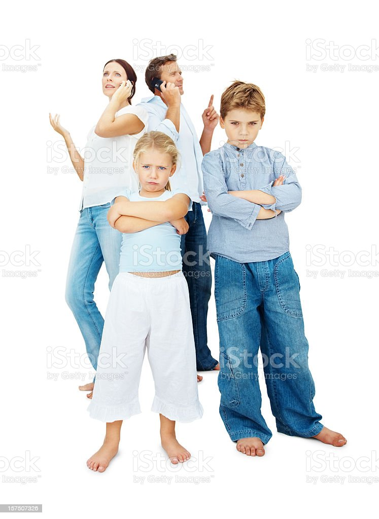 Serious children with parents talking on cellphone in the background royalty-free stock photo