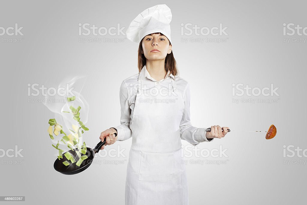 Serious cook woman holding a pan with creative cuisine stock photo