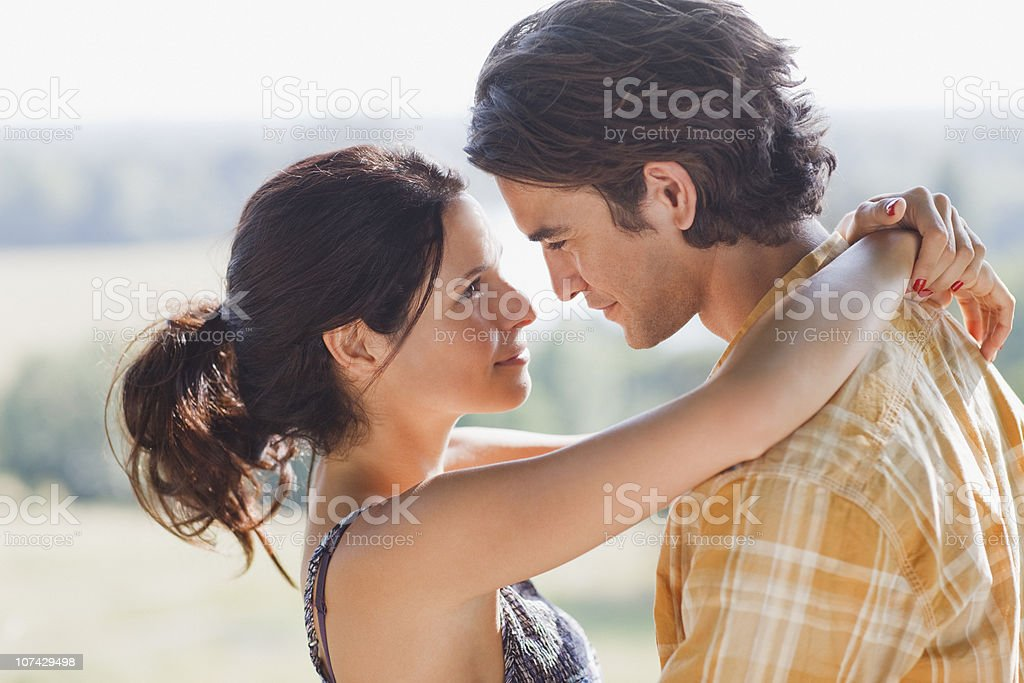 Serious couple hugging outdoors stock photo