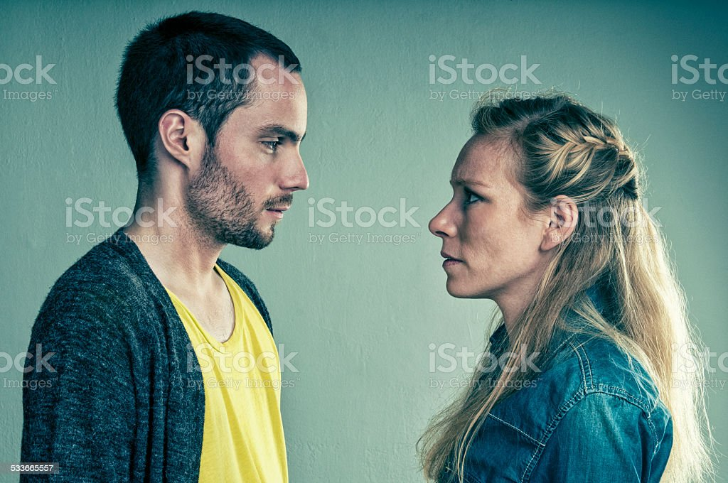Serious couple look at each other stock photo