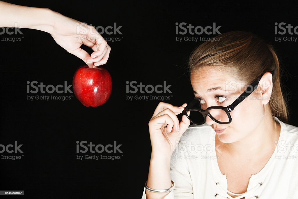 Serious, disapproving teacher looks over spectacles at offered apple
