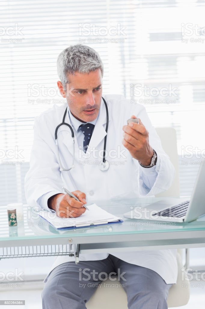Serious doctor looking a medication for a prescription stock photo