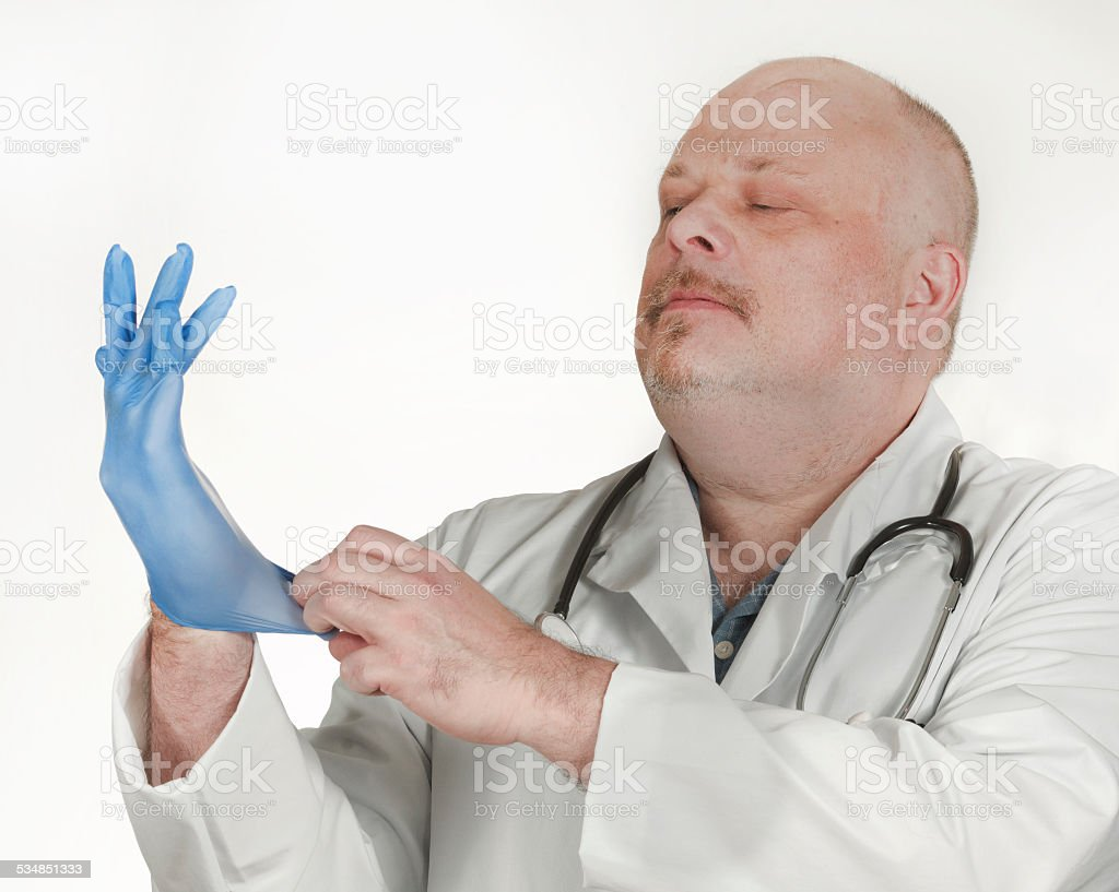 Serious Doctor Pulling on a Rubber Glove stock photo