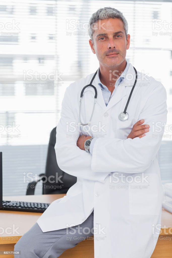 Serious doctor sitting on desk with arms crossed stock photo