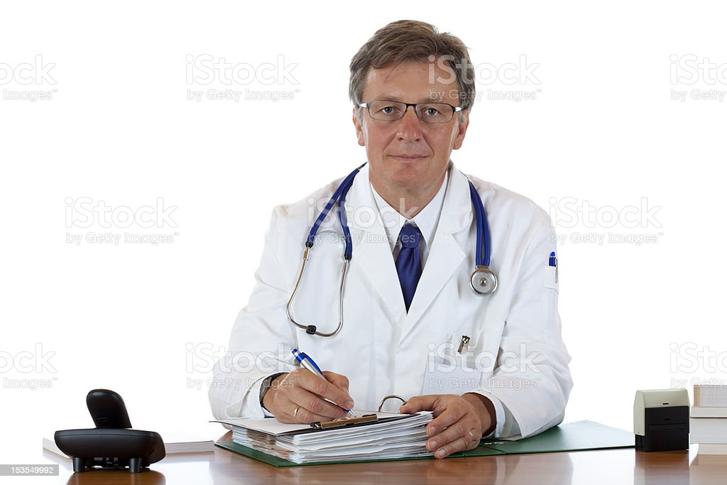 Serious elderly doctor writes down medical history royalty-free stock photo
