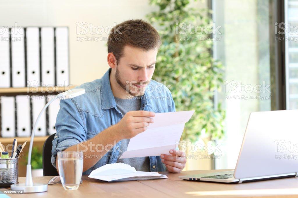 Serious entrepreneur reading a letter stock photo