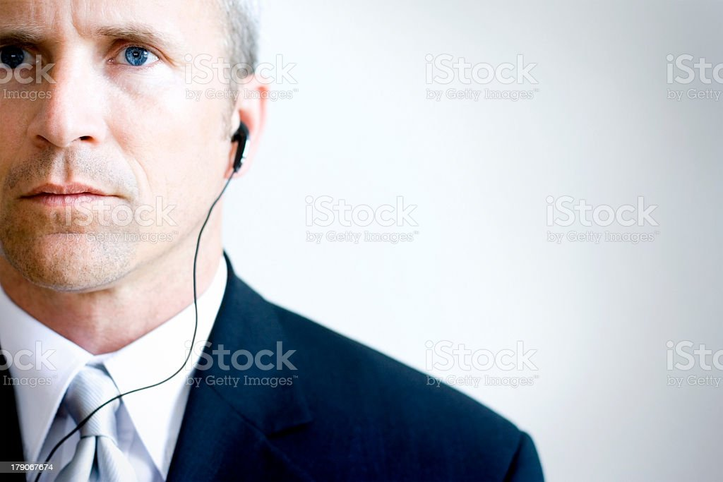Serious face man with suit and tie listening with earbuds stock photo