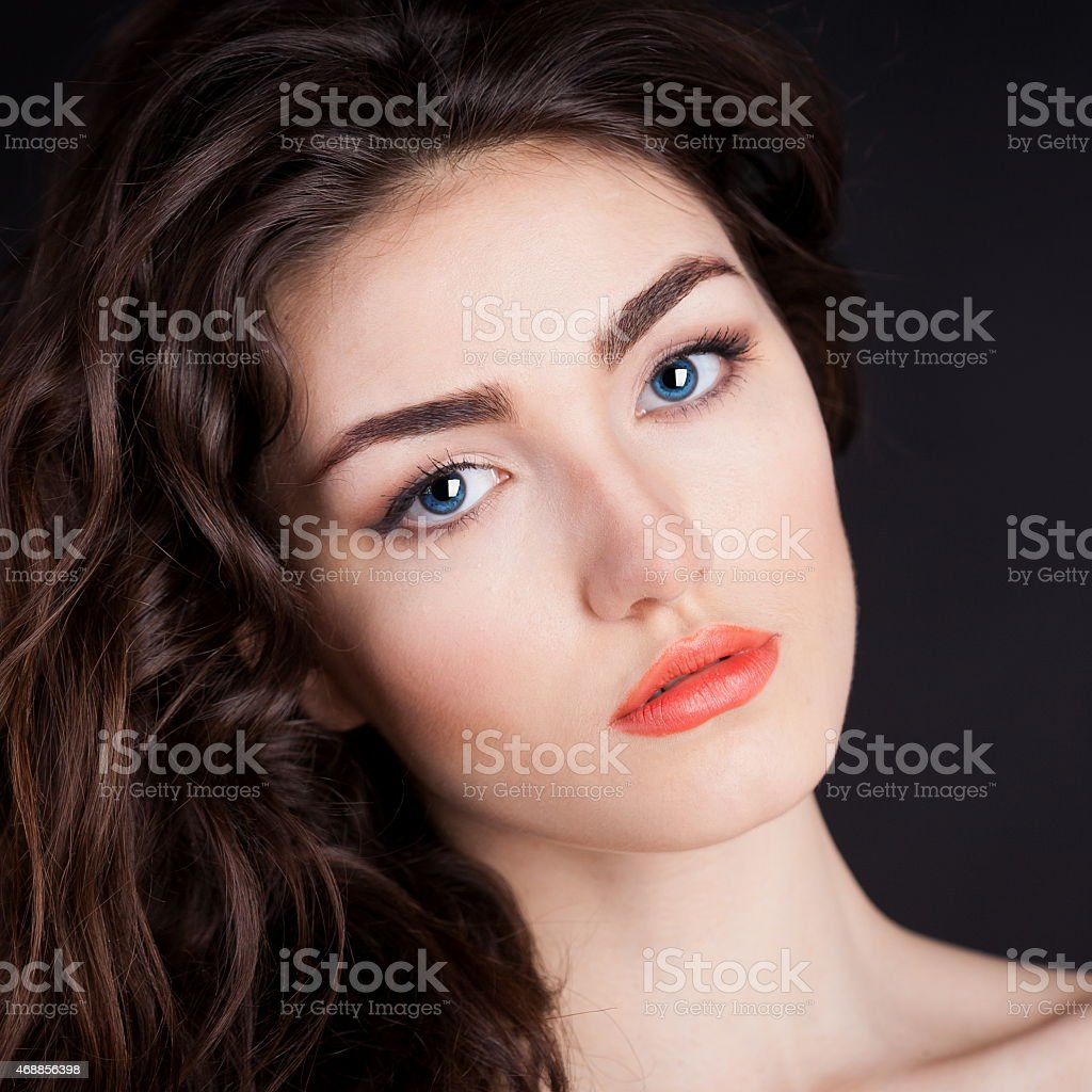 serious face with blue contact lenses, black background stock photo