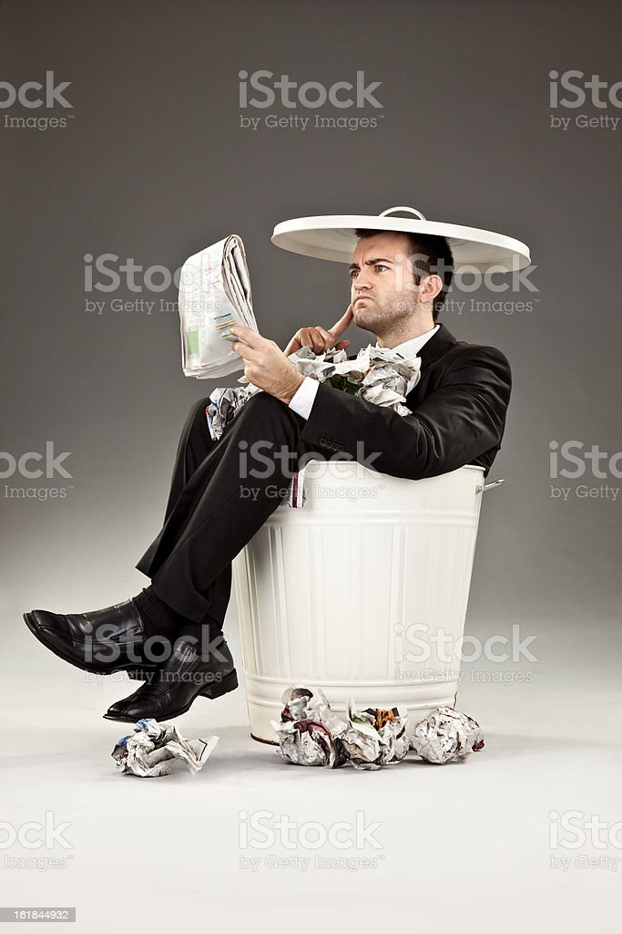 serious failure business man newspaper read in trash can stock photo