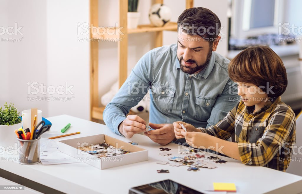 Serious father and son making picture of puzzles stock photo