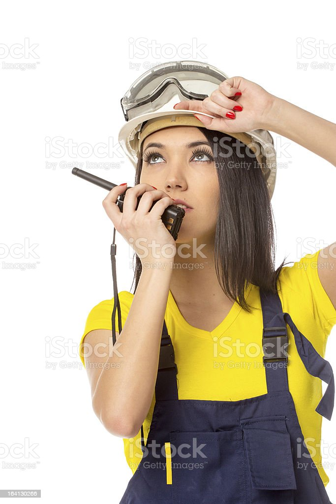 Serious female construction worker talking with a walkie talkie royalty-free stock photo