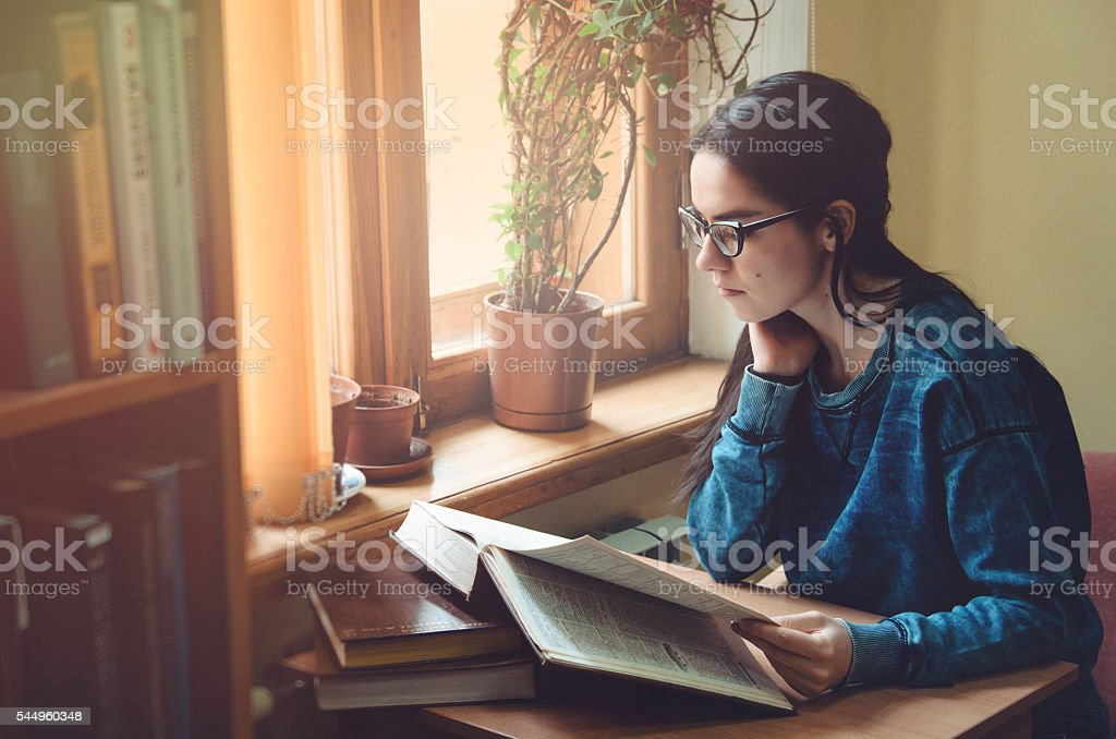 Serious female hipster student reading book and sitting at the stock photo