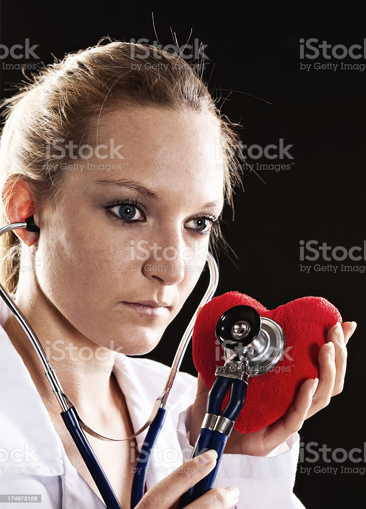 Serious female medical professional checks red velvet heart with stethoscope royalty-free stock photo