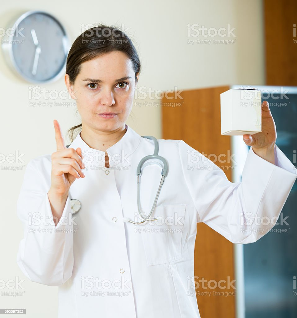 Serious female physician warning of faulty drugs stock photo