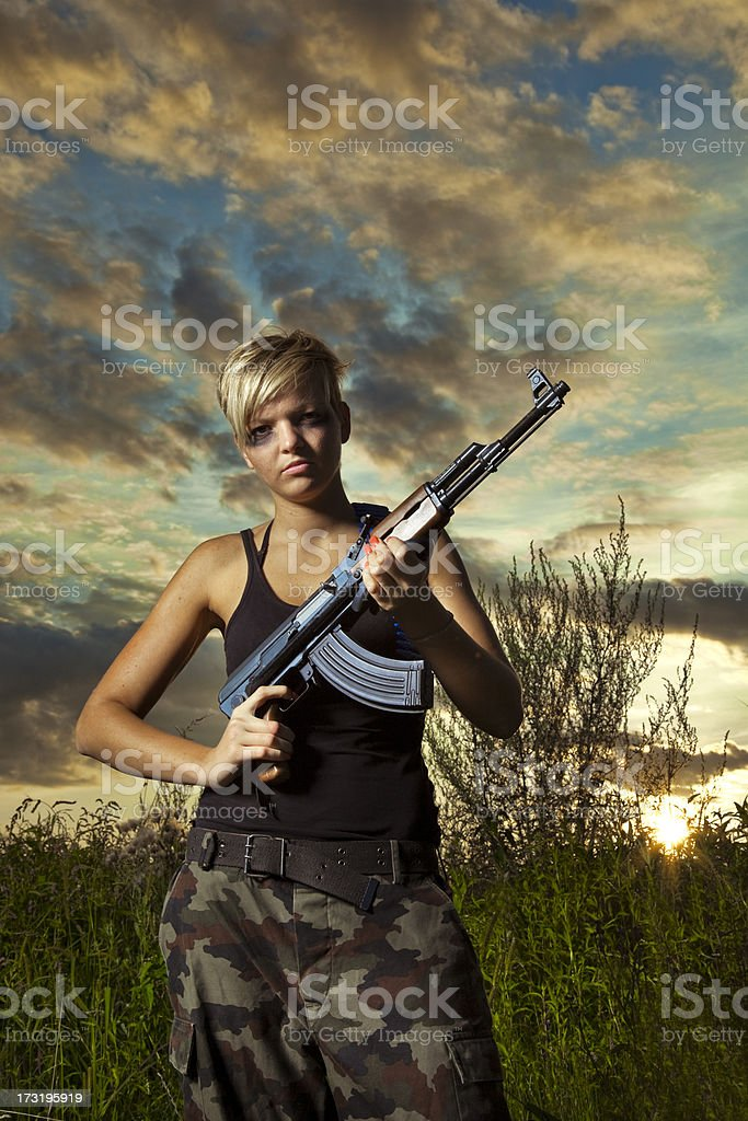 Serious female soldier holding AK47 stock photo