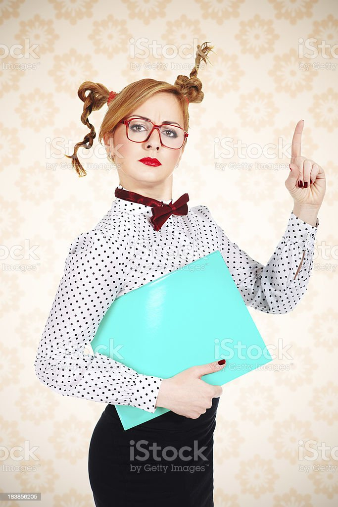 Serious female teacher wearing glasses posing with green folder royalty-free stock photo