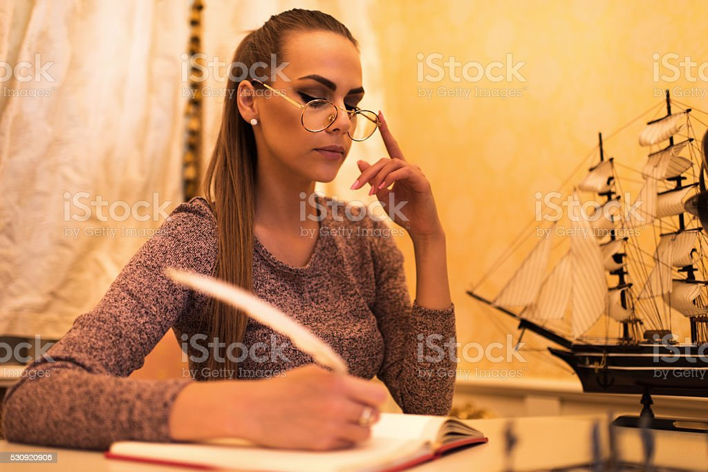 Serious female writer writing a story with quill pen. stock photo