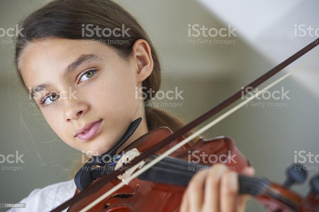 Serious girl playing violin stock photo