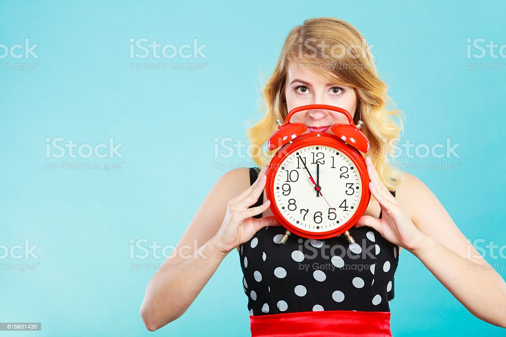 Serious girl with alarm clock on blue. stock photo