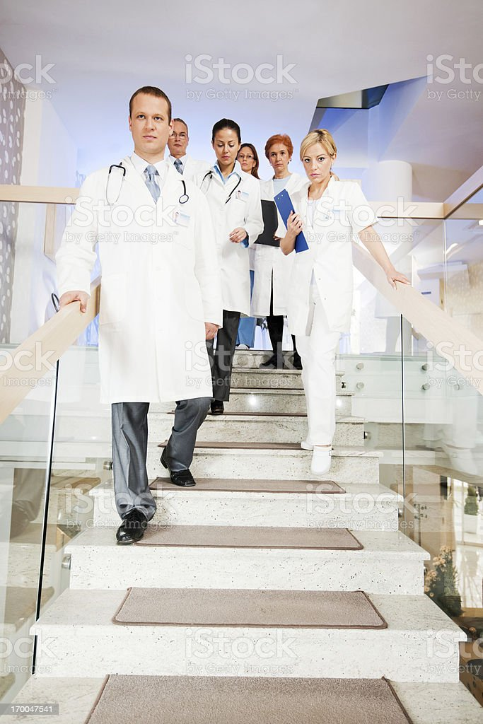 Serious group of doctors walking down the stairs. royalty-free stock photo