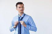 Serious Handsome Elegant Young Man Knotting Tie
