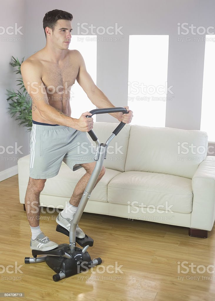 Serious handsome man training on stair climber stock photo