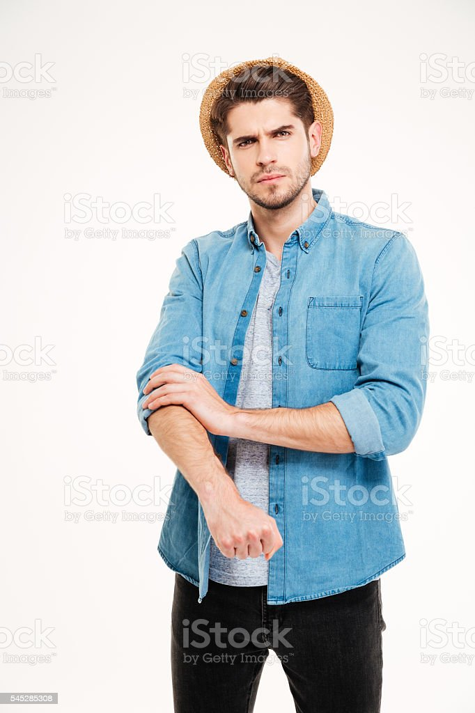 Serious handsome young man standing and rolling up his sleeves stock photo