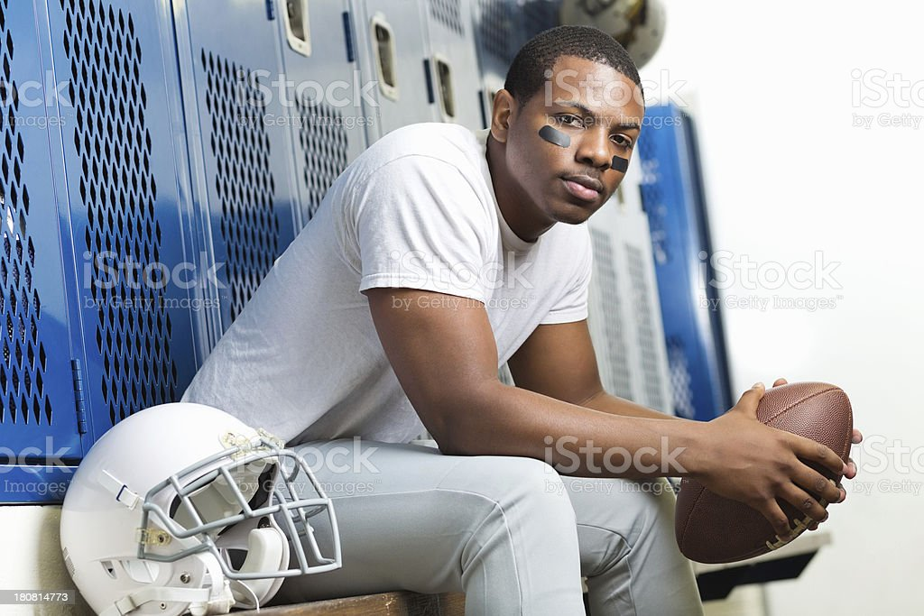 Serious high school football player in locker room after game stock photo