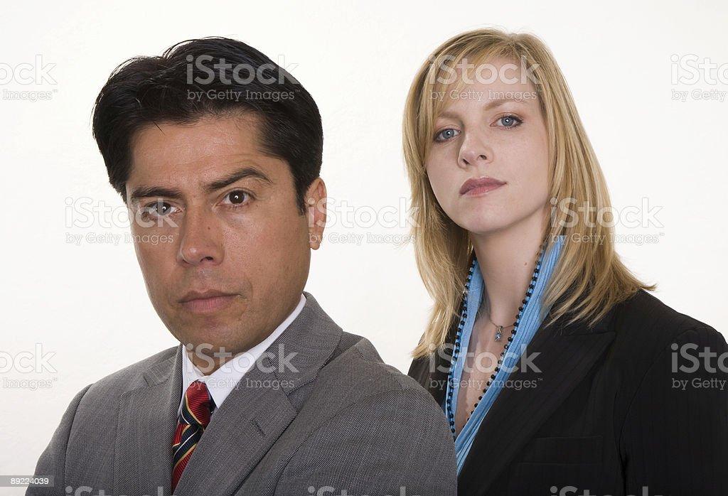 Serious Hispanic businessman and Caucasian businesswoman pose stock photo