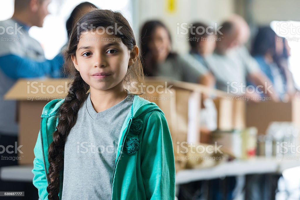 Serious Hispanic child in front of volunteers sorting food donations stock photo