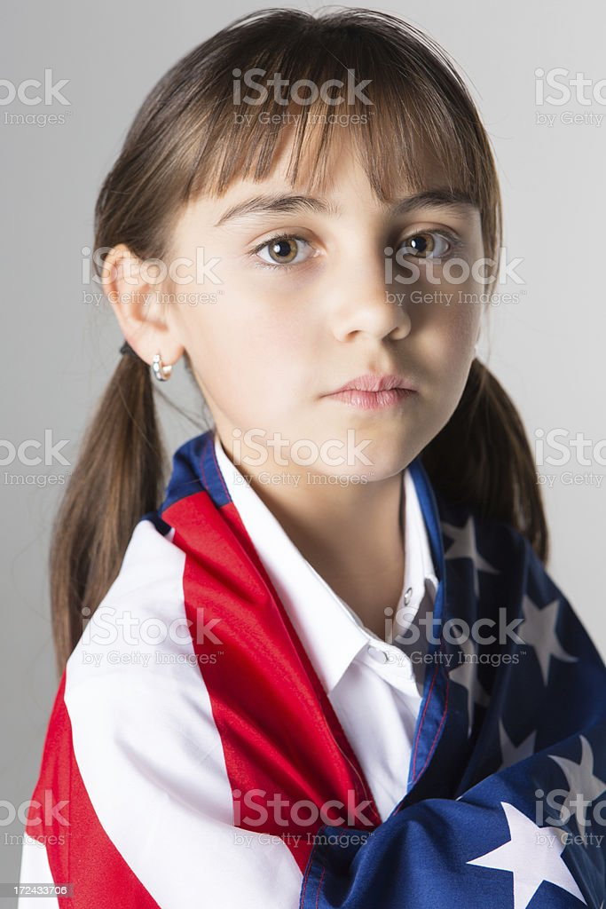 Serious Hispanic elementary girl with American flag; studio shot royalty-free stock photo