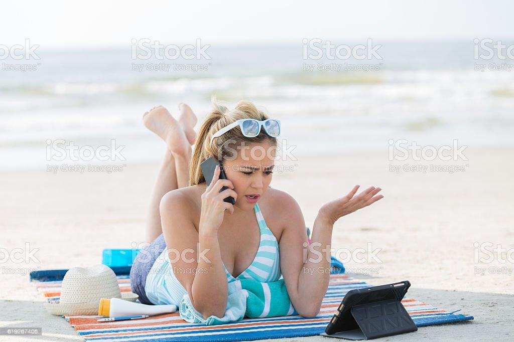 Serious Hispanic woman uses smart phone on the beach stock photo