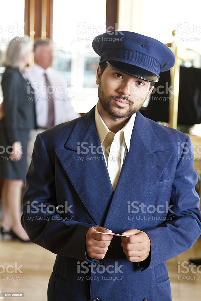 Serious hotel door man in front of guests at lobby stock photo