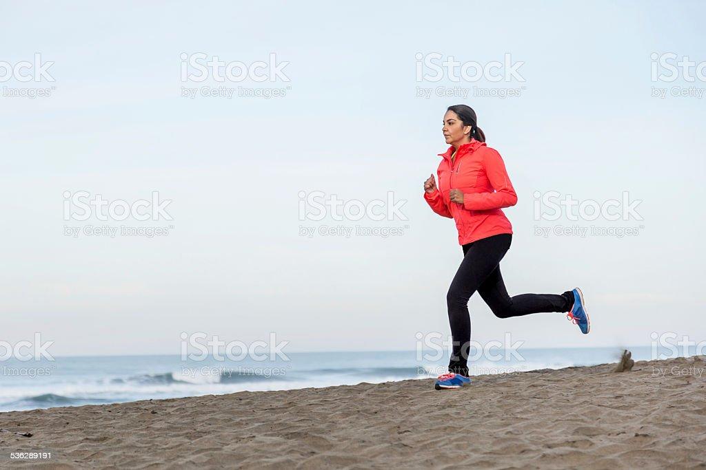 Serious Latino Woman Running on Beach stock photo