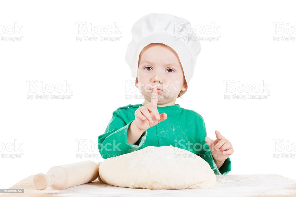 Serious little boy, dough for the cookies, isolated on white stock photo