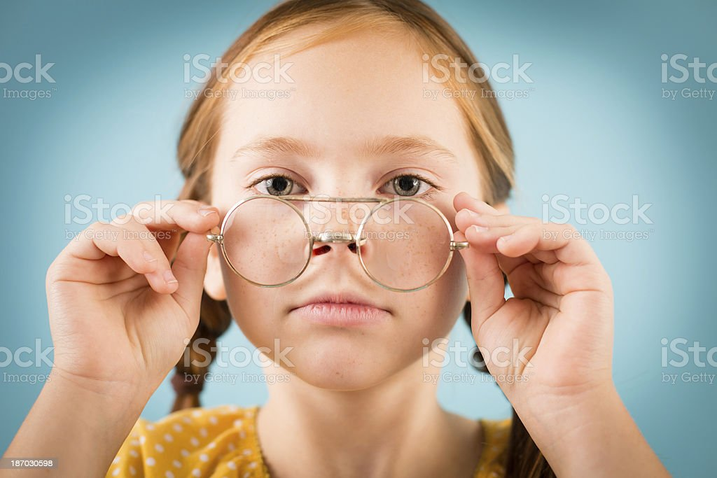 Serious Little Girl Looking Over Top of Her Nerdy Glasses royalty-free stock photo
