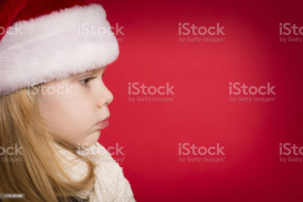 Serious Little Girl Wearing Santa Hat, With Red Background royalty-free stock photo