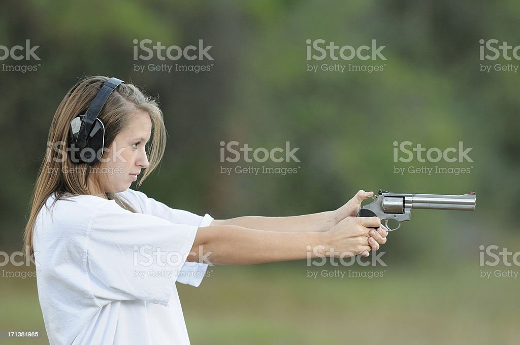 Serious looking girl aiming large pistol royalty-free stock photo
