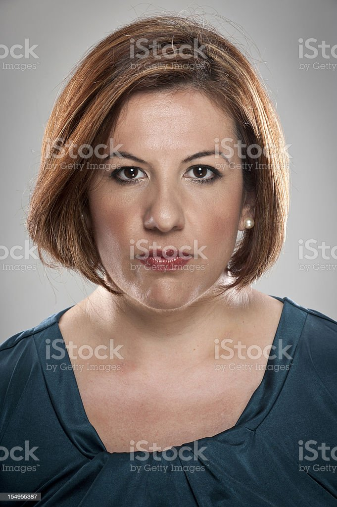 A serious looking Hispanic Woman with a white background royalty-free stock photo