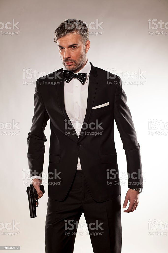 Serious looking man in a suit with a gun stock photo