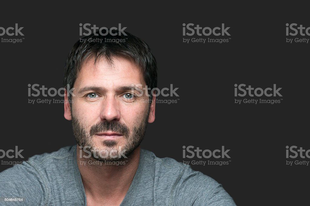 serious looking man portrait isolated on gray stock photo
