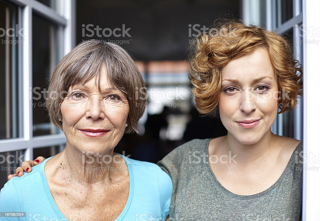 serious looking mother and daughter standing at the window royalty-free stock photo