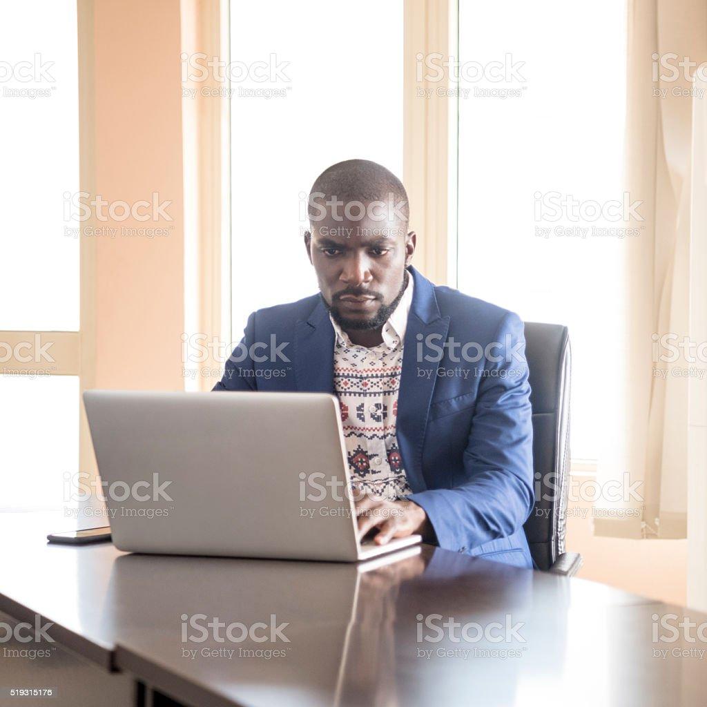 Serious looking Nigerian businessman using laptop stock photo