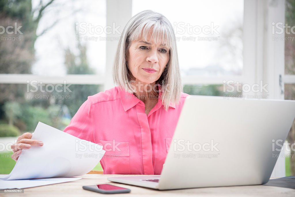 Serious looking senior woman with laptop and paperwork stock photo