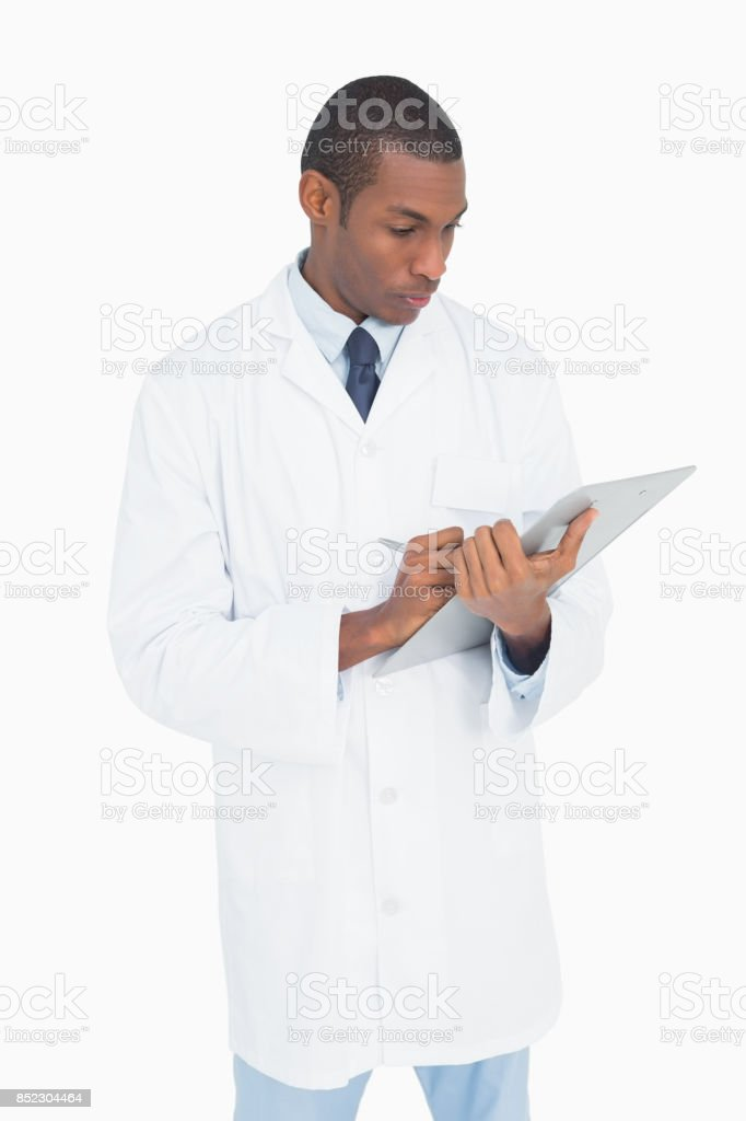 Serious male doctor writing on clipboard stock photo