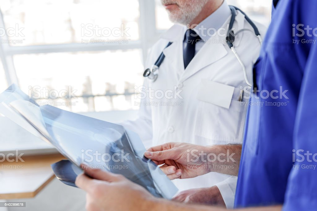 Serious male doctors analyzing roentgen picture stock photo