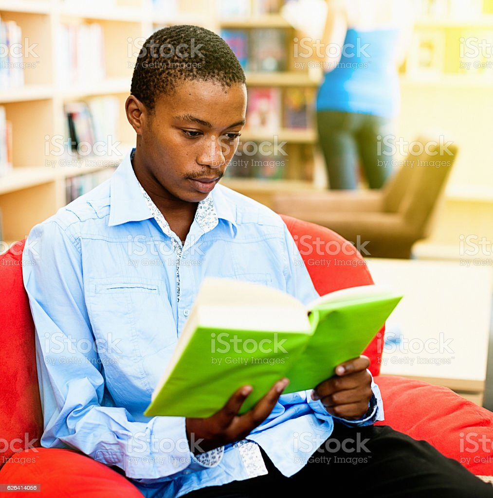 Serious male student sits studying in campus library stock photo
