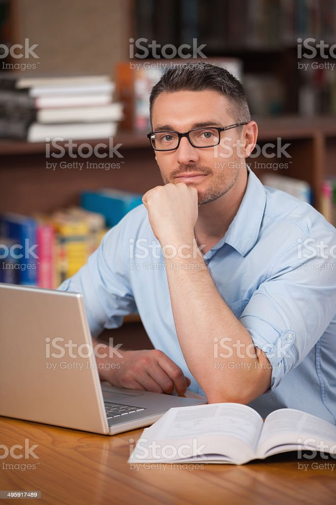 Serious male student using laptop in college library royalty-free stock photo